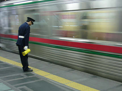 Japanese train station attendant bowing to train